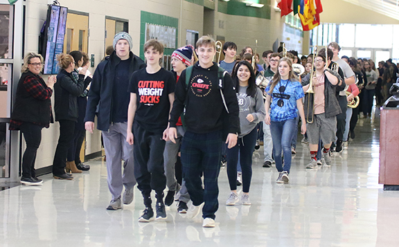De Soto High School wrestlers Jackson Mocca, Zak Kalafut, Lane Warner and Luke Barger walk in front of the band during their State send-off on Thursday, Feb. 21.