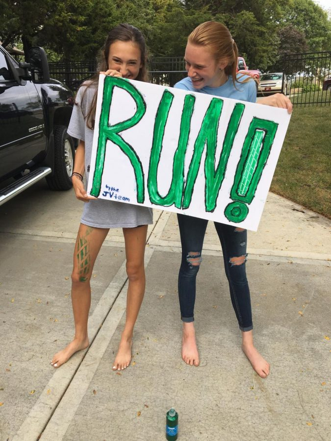 Junior cross country runners Lane Hileman and Erin Pickert pose with a sign they made at a team dinner on Sept. 17, 2017 for a homecoming parade.