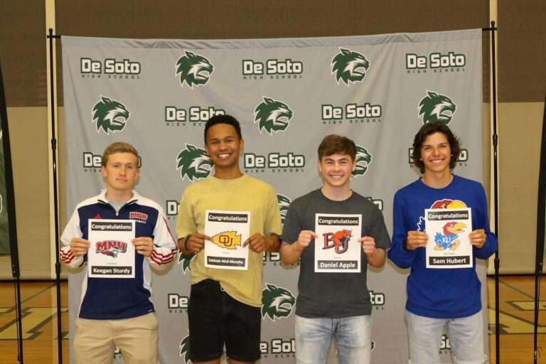 Seniors Keegan Sturdy, Zekkiah Hird, Daniel Apple, and Sam Hubert stand with their certificates at college signing April 17.