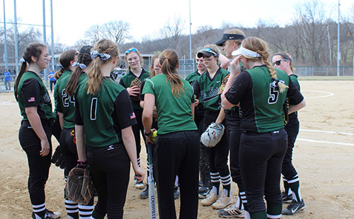 The softball team huddles together for a pregame talk before their games against Leavenworth High School on March 27.
