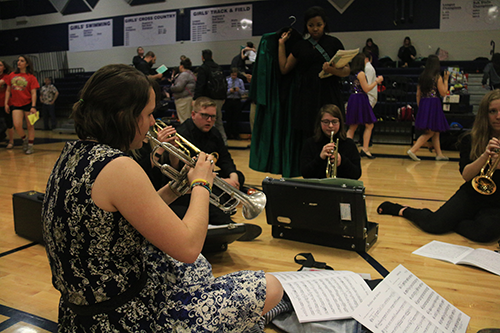Senior Adriana Feener warms up in the gym with members of the trumpet quintet at Mill Valley High School before their performance on April 6, 2019.
