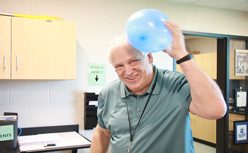 DHS long-term physics sub Ron Lewis demonstrates the physics of rubbing a balloon on one's head.
