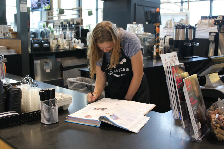 Senior Aspen Grieshaber works on her AP Psychology homework during her down time at work at the Lenexa Public Market on Sept. 25.
