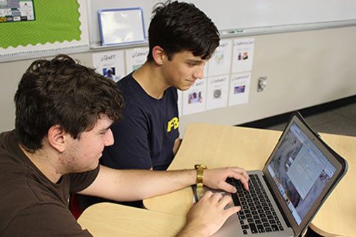 Senior Alex Bates assists a student with a technology problem relating to his Macbook on Sept. 9.