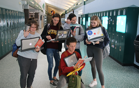 De Soto High School seniors display the realities of senior year while holding all of their homework, coffee, books and MacBooks on Nov. 7, 2019.