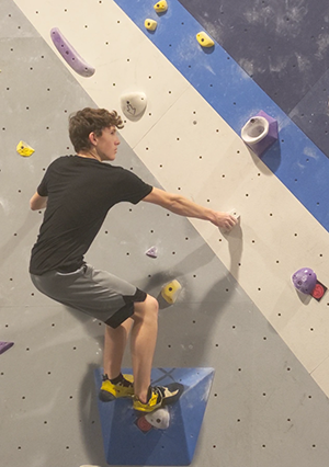 Sophomore Ryan Handley prepares to make a jump to the next hold while rock climbing at Sequence climbing gym.