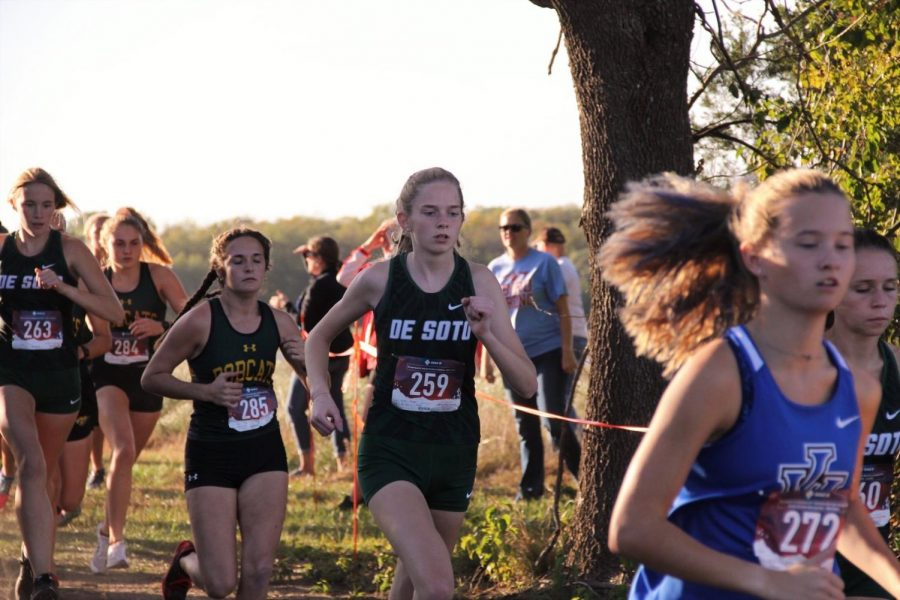 Senior Justine Wheeler races in a varsity girls 5K cross country meet.