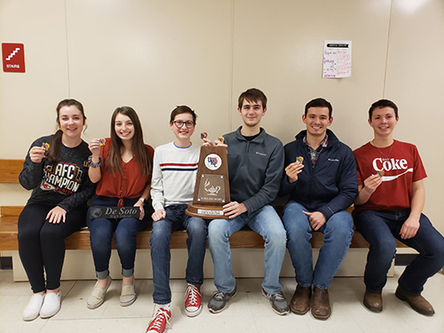 Scholars Bowl UKC team poses with medals and trophy