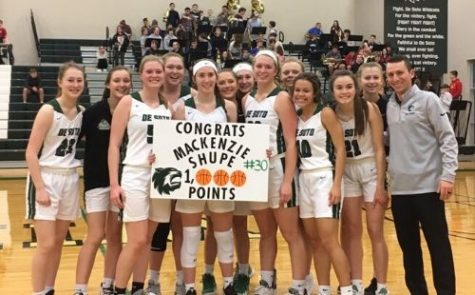 The De Soto High School varsity girls' basketball team poses with senior Mackenzie Shupe to congratulate her on reaching one thousand total career points after the game against Turner High School on Feb. 11.