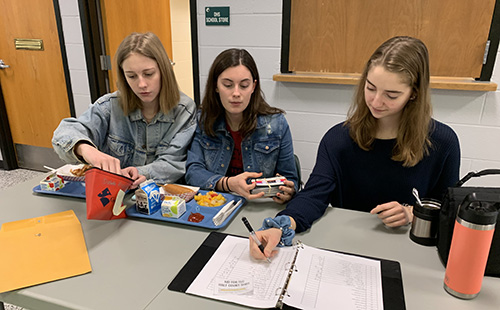 Sophomore Student Council Executives, Reagan Ames, Josie Butler and Brenna Johnson sell Winter Homecoming tickets at lunch on Feb. 6.