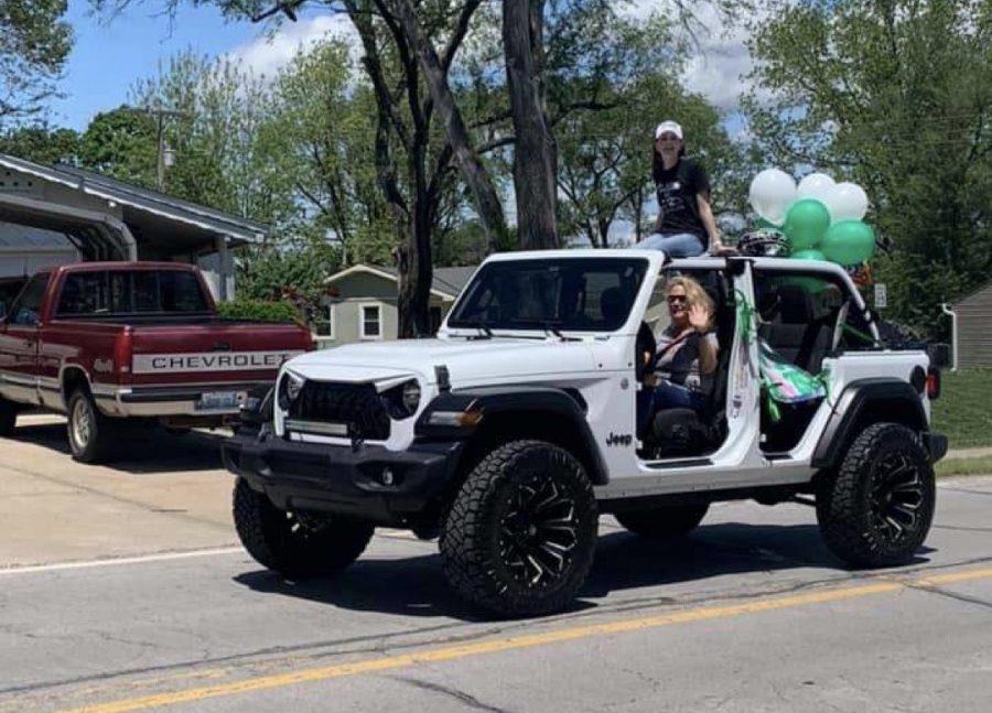 Senior Mason Johannes rides through celebratory graduation parade with her mom and dad on Sunday, May 17.