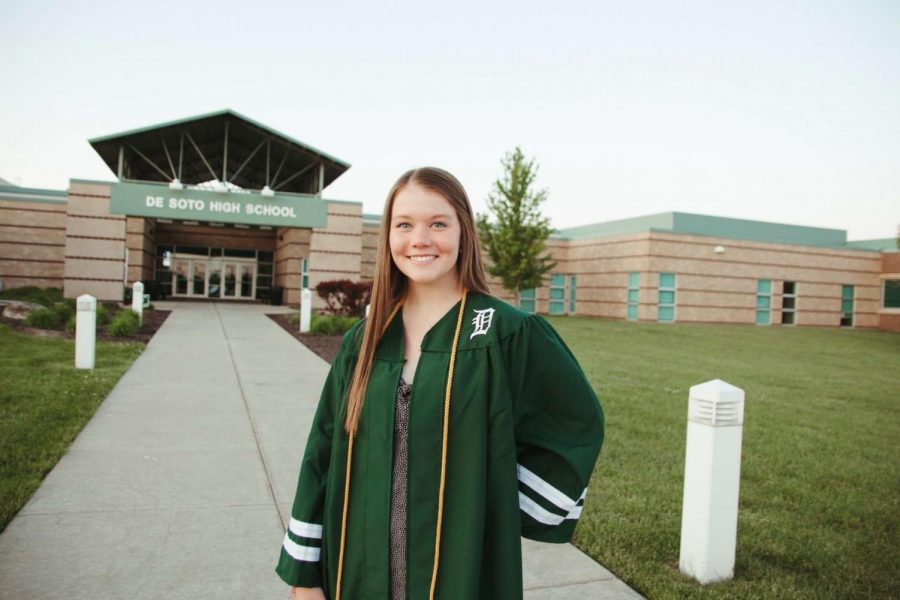 Senior Addie Gress poses for pictures in her graduation gown at De Soto High School on Friday, May 8.