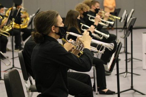 Several trumpet players from the De Soto High School band perform with their masks and bell covers to minimize the spread of germs during their concert on Dec. 14.