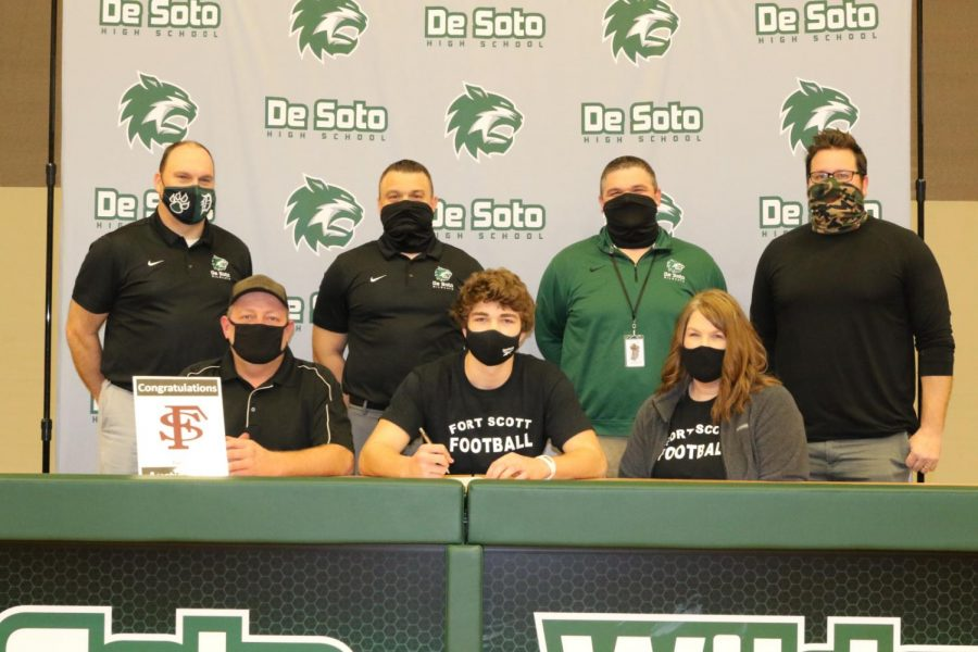 Austin Tabor signs to Fort Scott Community College alongside his parents and coaches on Feb. 3, 2021