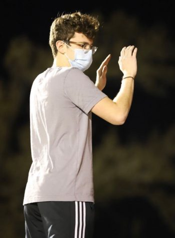 Junior Kendan Powers conducts the DHS Band during a performance at a DHS football game.