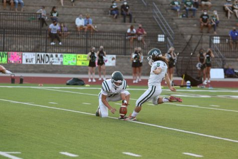 Senior Tyler Schultze holds the ball for senior Luke VanBooven as he kicks a field goal during a game against Lawrence Free State High School on Sept. 4, 2020.