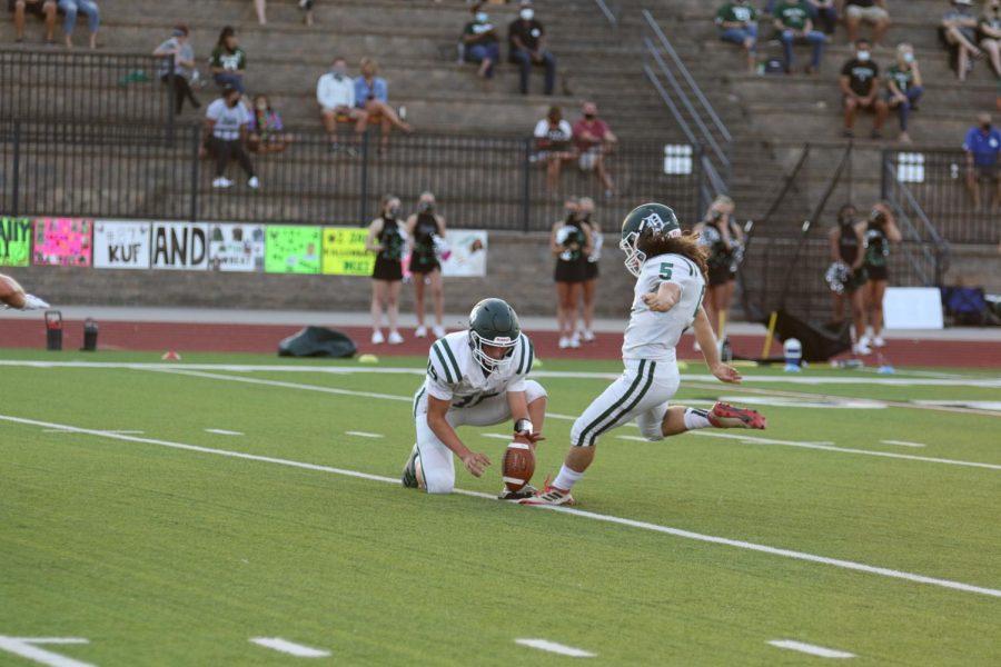 Senior+Tyler+Schultze+holds+the+ball+for+senior+Luke+VanBooven+as+he+kicks+a+field+goal+during+a+game+against+Lawrence+Free+State+High+School+on+Sept.+4%2C+2020.