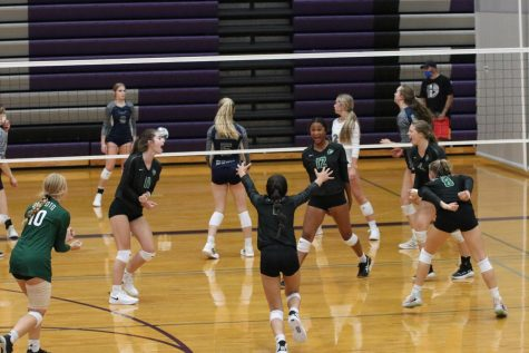The varsity volleyball team celebrates after gaining a point against Louisburg on Sept. 3.